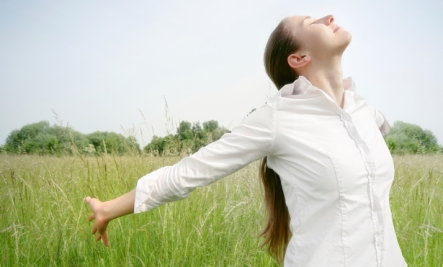 woman taking deep breath in field